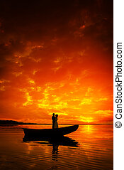 Silhouette of a couple kissing in boat on river in sunset -...