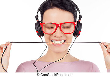 It is her favorite song. Beautiful young woman in red glasses and headphones listening to the music and keeping eyes closed while isolated on white
