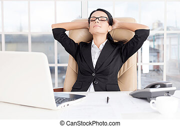 Chill time. Cheerful young business woman holding head in hands and keeping eyes closed while sitting at her working place