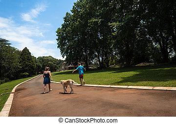 Girls Walking Driveway Dog - Young girls walking home with...