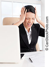 Emotional stress. Young business woman holding head in hands and shouting while sitting at her working place