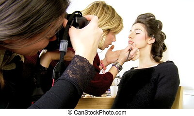 Fashion model being photographed during makeup