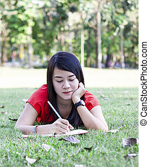 beautiful young brunette woman writing in her diary
