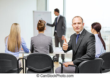 businessman with team showing thumbs up in office -...