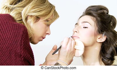 Touch up of lips of female model - Makeup artist working on...