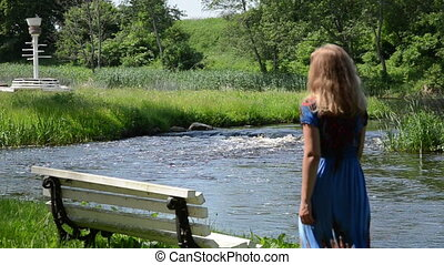 girl on bench by stream - blonde young girl with a blue...