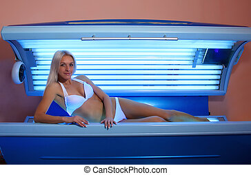 woman sunbathing in the solarium - Beautiful slim blonde...
