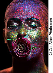 Glitter makeup on a beautiful woman face on a black...
