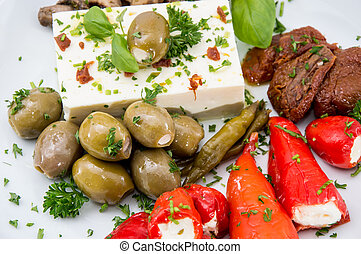 Different types of Antipasto on a plate against wood
