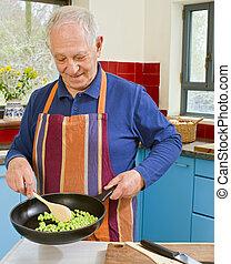 senior cooking - senior man cooking in his kitchen