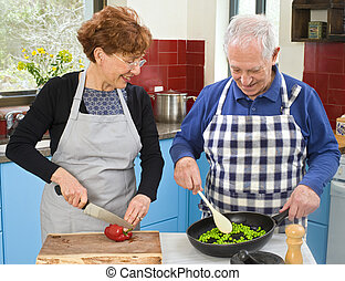 senior couple cooking at thier kitchen at home