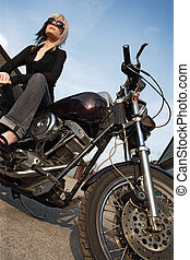 Motorcycle girl angle - A beautiful blonde female sitting on...