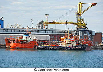 Bunker ship fuel replenishment tanker under port crane,...