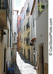 Narrow street in Alfama, Portugal - Narrow cobblestone...