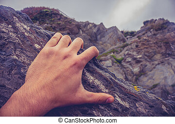Mans hand on rock