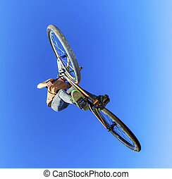 boy going airborne with his dirt bike and showing a non...