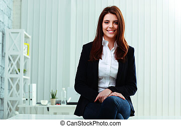 Young cheerful businesswoman sitting on the table in office