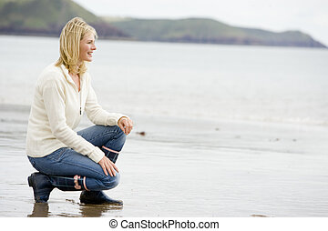 Woman crouching on beach smiling