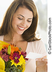 Woman holding flowers and reading note smiling