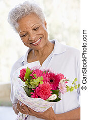Woman holding flowers and smiling