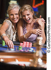 Two women in casino playing roulette and smiling (selective...