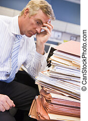 Businessman in cubicle with laptop and stacks of files
