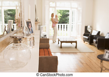 Woman standing in living room holding baby