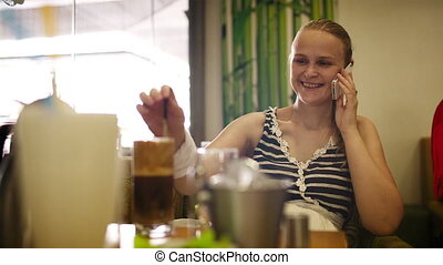 Woman in cafe speaking on the phone.