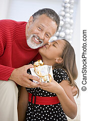 Grandfather Giving His Granddaughter A Christmas Present