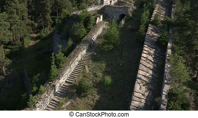 Cyclist running down stairway in a castle during bycicle...