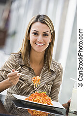 Woman at restaurant eating spaghetti and smiling (selective...