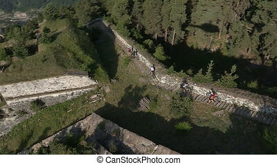 Cyclists running down stairway in a castle during bycicle...