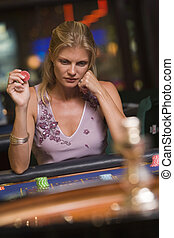 Woman in casino playing roulette and holding chip (selective...