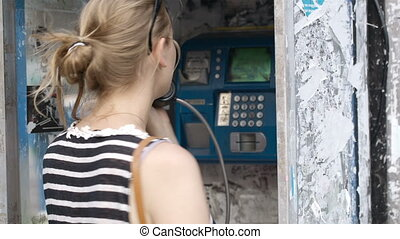 Attractive woman using a public telephone