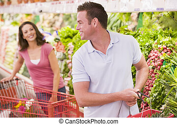 Young couple shopping for vegetables at a grocery store
