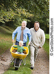 Two men walking on path outdoors pushing baby in wheelbarrow and smiling (selective focus)