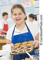 Female student holding a tray of tarts in cooking class