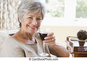 Woman in living room with glass of wine smiling