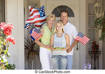 Family at front door on fourth of July with flags and...