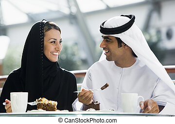 Couple at restaurant eating dessert and smiling (selective...