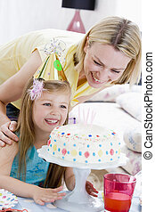 Mother and daughter with birthday cake smiling