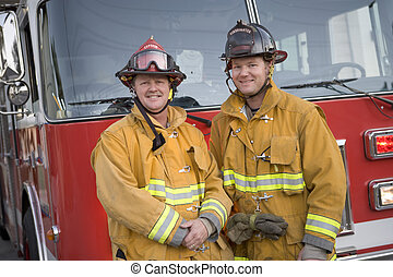 Two firemen standing in front of fire engine