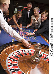Group of people in casino playing roulette and smiling...