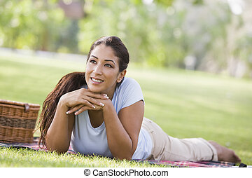Woman lying outdoors at park with picnic basket smiling...