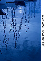 Blue water reflection of sailboats boats poles in waves