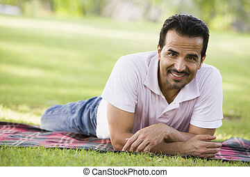 Man lying outdoors at park smiling (selective focus)
