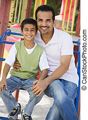 Father and son sitting on playground structure smiling...