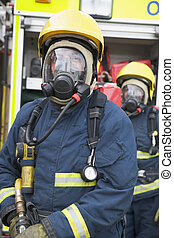 Two firemen in masks standing near fire engine depth of...