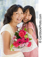 Granddaughter and grandmother holding flowers and smiling
