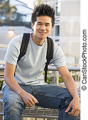 Man sitting on bench outdoors smiling (selective focus)